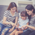 Mother, Aunt and kid having time together lerning with using tab